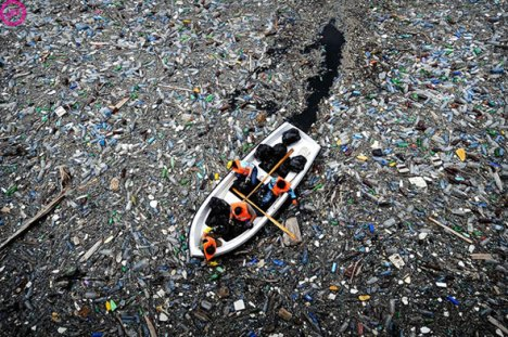 A floating boat surrounded by plastic inside an ocean gyre