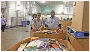 Kevin Malinowski, a consultant at Green Marketing, and Maurice Jackson, co-manager of Goodwill Columbus, stand behind piles of books that were donated. The books will be recycled through a new partnership between the two.Photo Courtesy of Green Marketing.