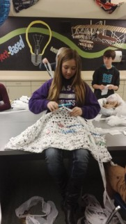 An eighth grader shows how easy it is to turn plastic bags into cushy bed mats for the homeless