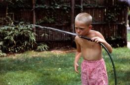 Boy Drinking Water from Garden Hose